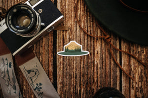 Respect Our Parks Park Ranger Hat Sticker with Trees and Mountains sitting on wood floor surrounded by hat and camera