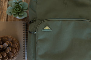 "Wildtree park ranger hat pin displaying words ""Respect our Parks"" pinned to backpack"