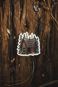 Find me in the woods cabin sticker sitting on log