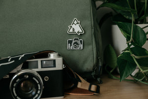 Recycle logo redesigned incorporating a mountain and tree pinned to a backpack above a camera pin and camera.