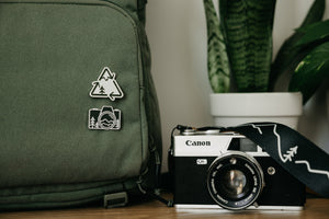 Two Wildtree pins attached to backpack next to film camera and plant