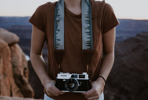 Women holding camera with Wildtree cactus and pine tree camera strap around neck