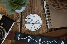 Load image into Gallery viewer, Circle Monument valley sticker on wood background surrounded by notebook, camera and succulent