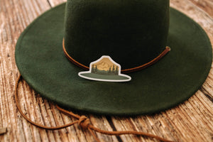 Green and Orange Park Ranger Hat Sticker sitting on Green hat