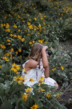 Load image into Gallery viewer, women sitting in flower feild photographing with Wildtree floral camera strap