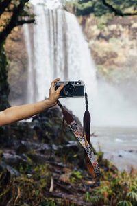 extended hand holding film camera with Wildtree Wildflower Floral camera strap attached