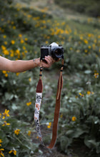 Load image into Gallery viewer, extended hand holding film camera with Wildtree Wildflower Floral camera strap attached