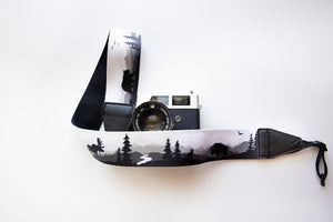 Wildtree Wildlife Camera Strap featuring Bear, Moose and Trees with mountain range background connected to Canon film camera