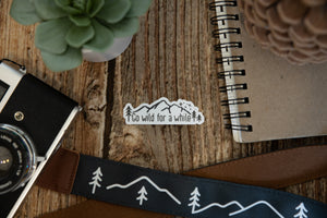 Wildtree go wild for a while sticker on wood background surrounded by notebook, camera and succulent