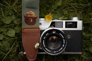 Smokey Bear camera strap next to flowers and film camera