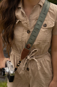Wildtree Smokey Bear Camera Strap attached to film camera around women's shoulder