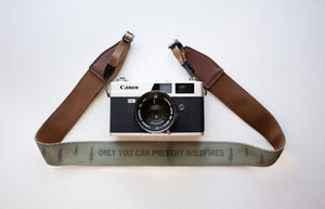 "Wildtree Smokey Bear Camera Strap with words ""Only you can prevent wildfires"" attached to film camera"