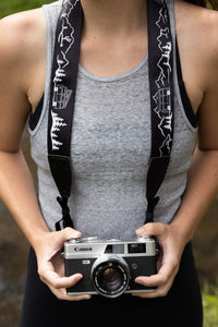 Women holding film camera with Wildtree Black and White Van life Camera strap featuring mountains, trees, cacti and VW Bus