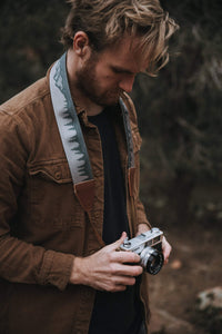 Man holding camera with Wildtree landscape camera strap around neck