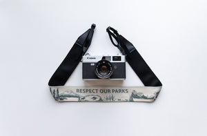 Wildree Respect our parks camera strap with black synthetic leather ends attached to film camera