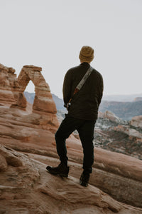 Man looking at Delicate Arch in Arches national park wearing National park inspired camera strap