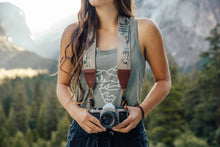 Load image into Gallery viewer, Women holding camera with Wildtree national park camera strap around neck