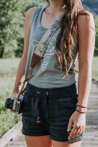 Women holding camera with Wildtree national park camera strap over shoulder