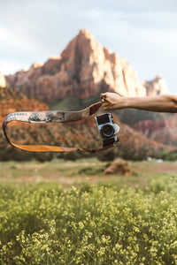 extended arm holding Wildtree national park camera strap in zion national park