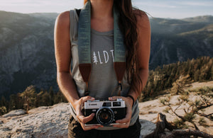 Women wearing Wildtree pinetree camera strap attached to camera