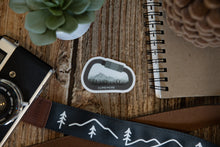 Load image into Gallery viewer, Climb More Carabiner Sticker on wood background surrounded by notebook, camera and succulent