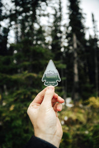 hand holding wildtree mt rainier sticker in front of a forest