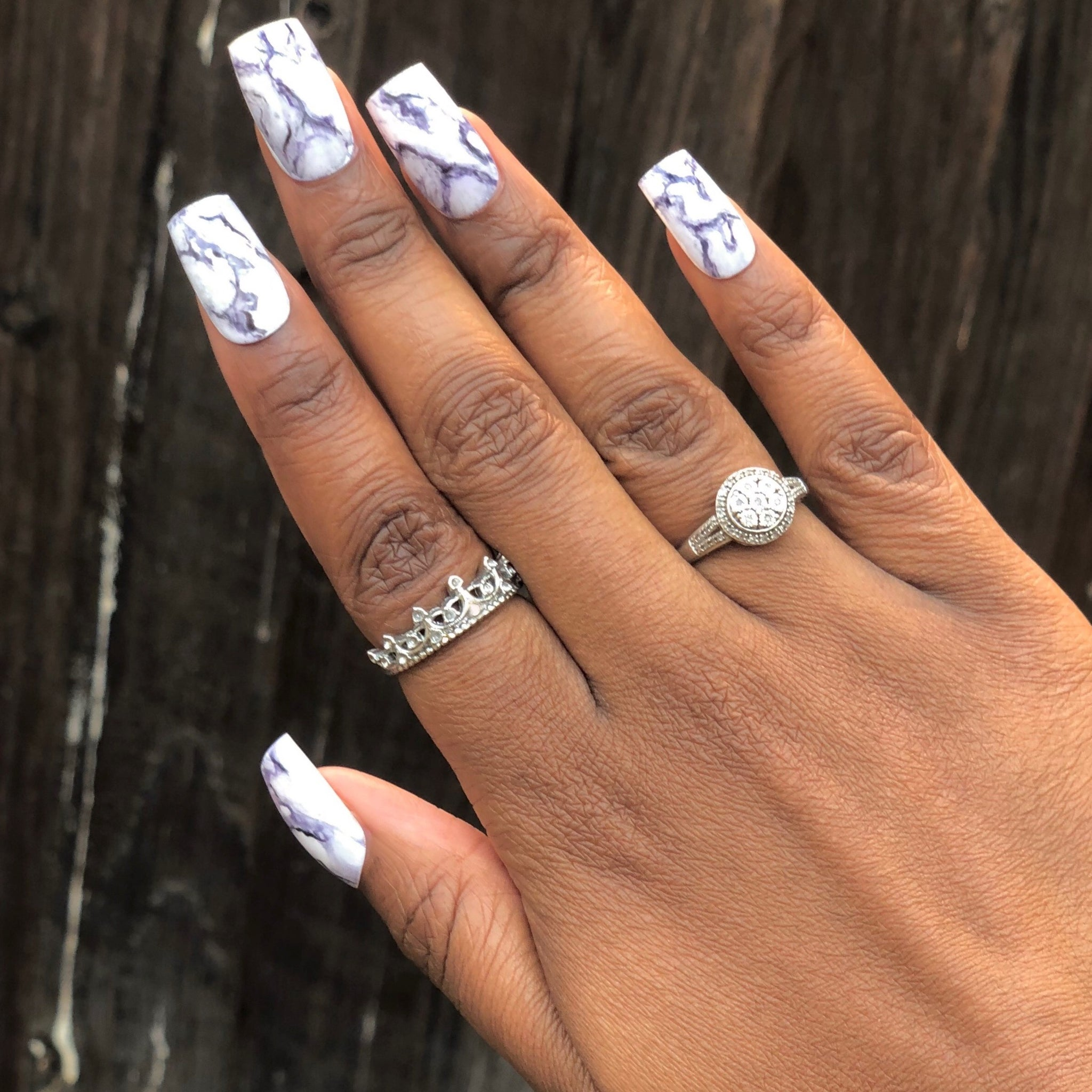 Manicure hand wearing marble press on nails.