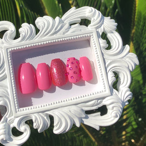 Pink press on nails with pink glitter on one nail and pink gems on another nail.