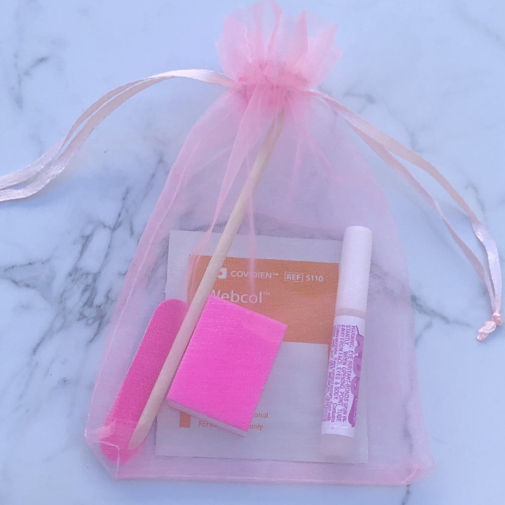 Press on nail application kit in pink bag with nail glue, nail file, nail buffer, alcohol wipe and cuticle pusher.
