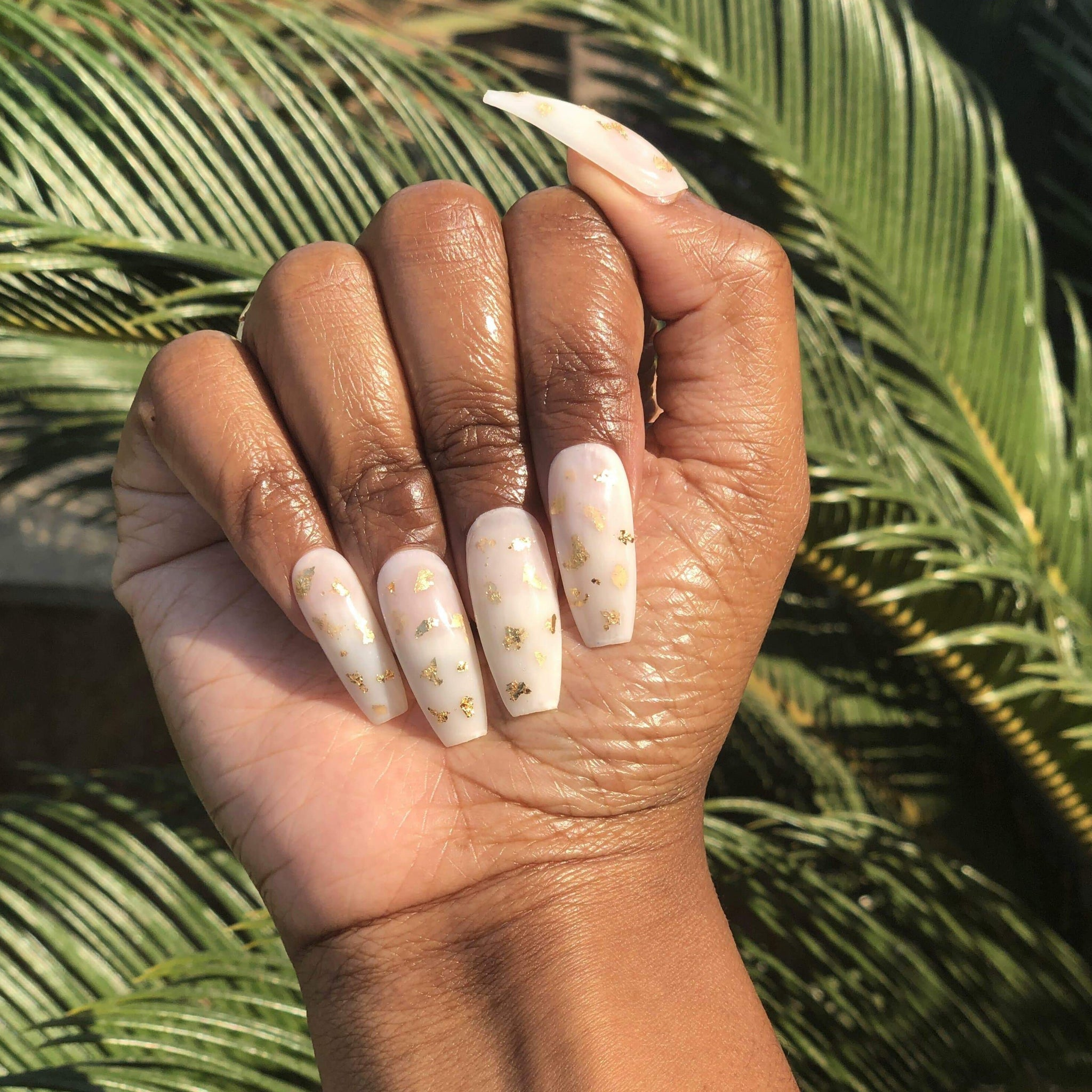 Manicure hand wearing gold foil milk bath press on nails.