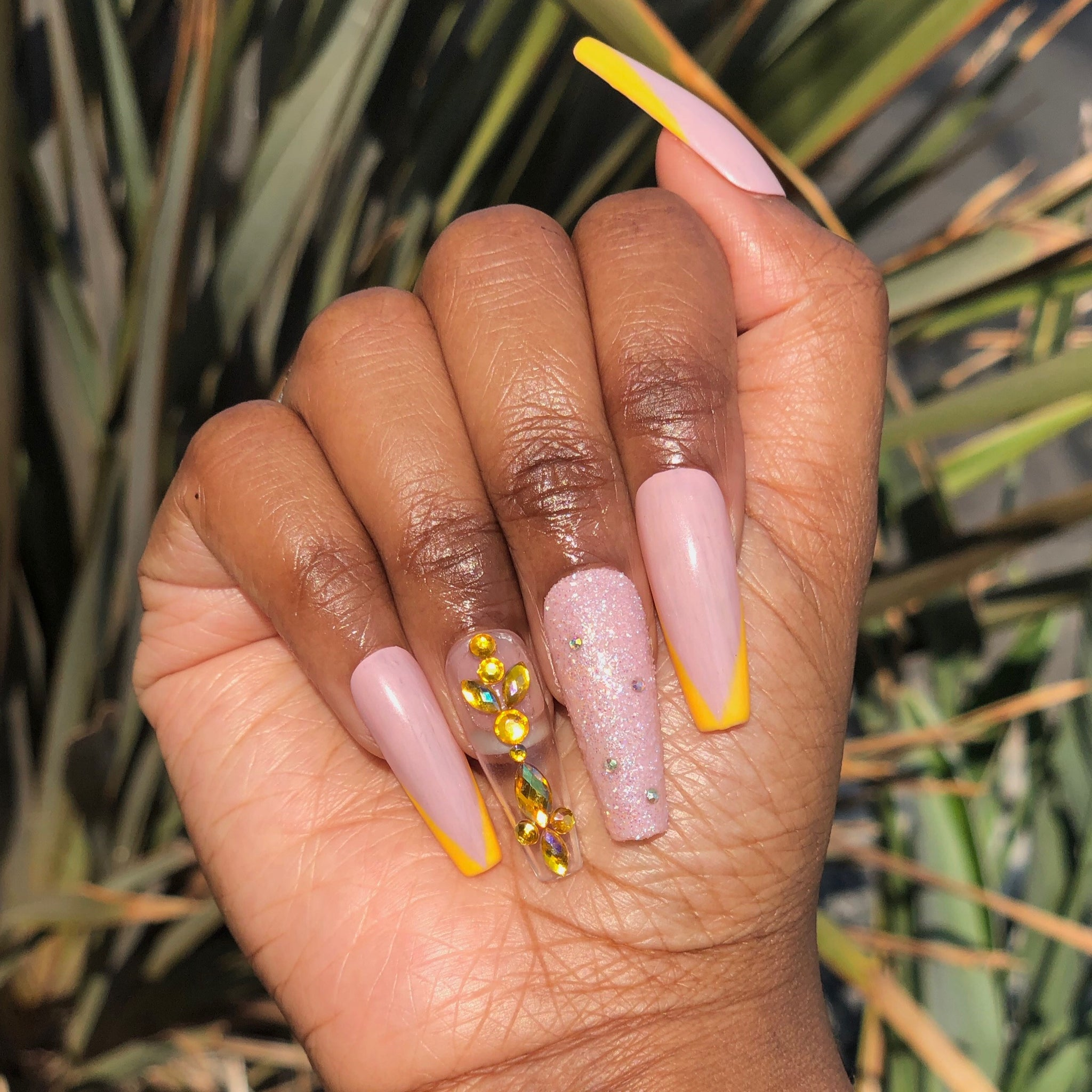 Manicure hand wearing tan press on nails with yellow French tip and multicolor yellow base  gems