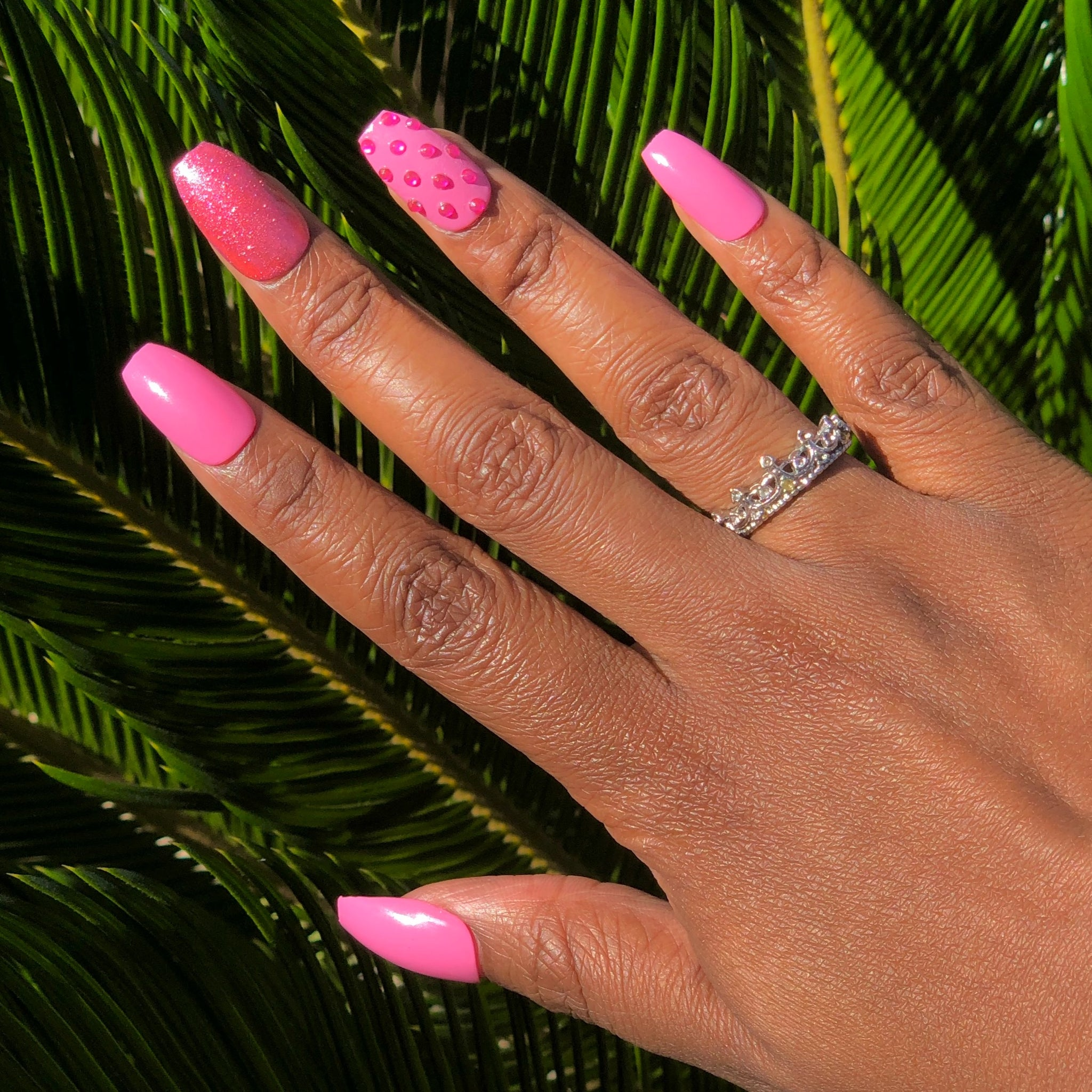 Manicure hand wearing pink nails with pink glitter on middle finger and pink rhinestones on ring finger.