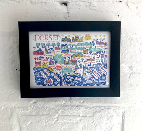 Framed, whimsical art print of Dorset by Julia Gash featuring cities, coast and landscape