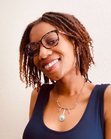 Photo of founder, Kendria Thompson, wearing glasses, a sterling silver gemstone necklace, and a blue, sleeveless top.