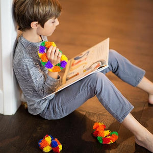 Boy Fidgeting with Tangle while reading Tangle Brain Tools Hardcover Book