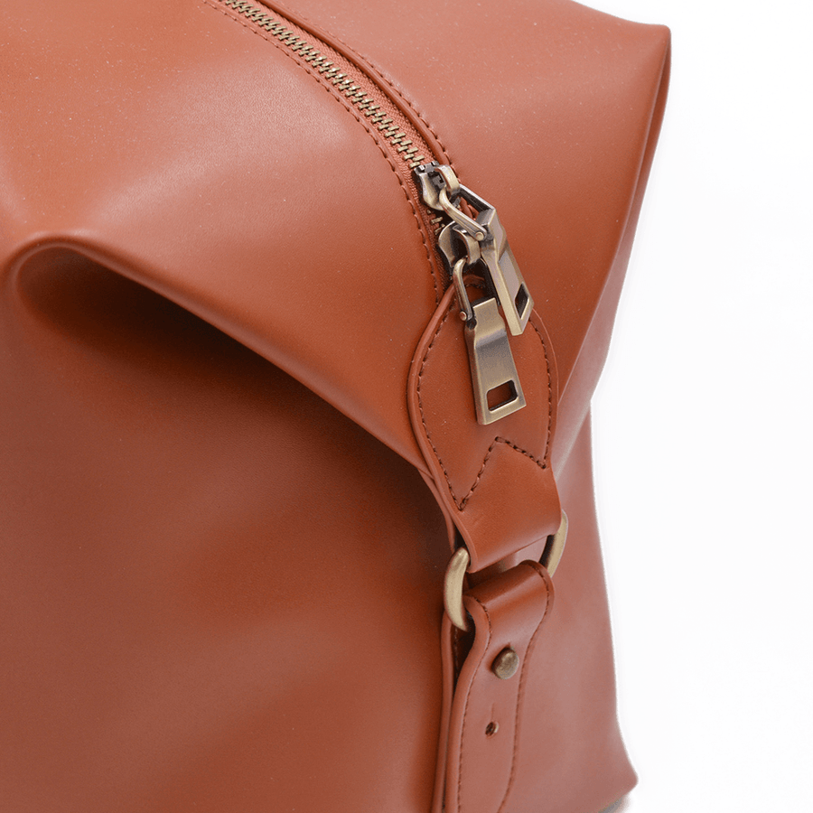 Close up of zipper on tan vegan leather duffel bag by Refined Traveler