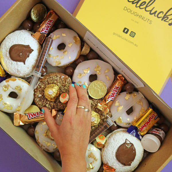 Donut box including twirl chocolate and chocolate syringes, and a hand holding a ferrero rocher cronut