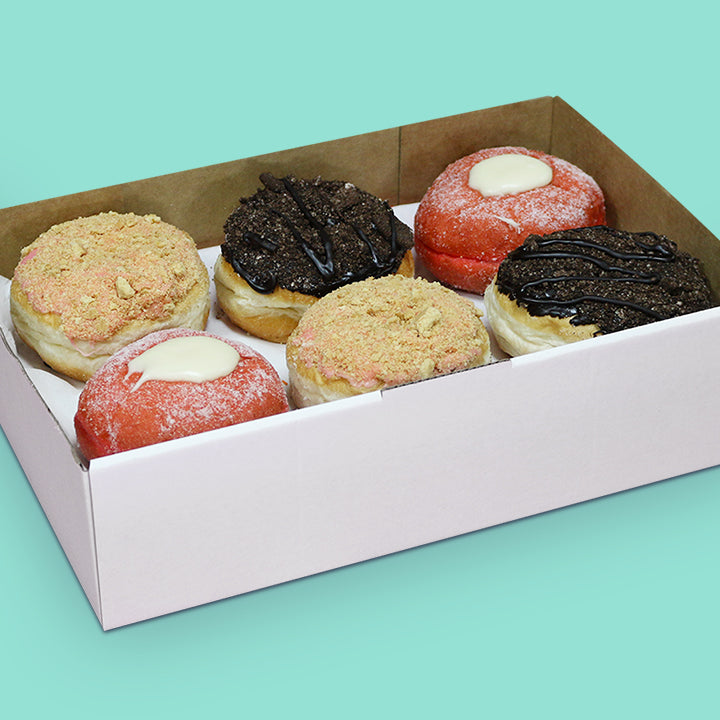 Gourmet vegan donut box with strawberry cheesecake, red velvet with cream cheese, and oreo cheesecake donuts