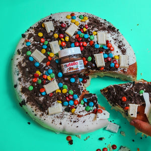 Round Hershey's white chocolate cake with oreo crumbs, mini m&m's, and Hershey's chocolate, topped with mini nutella jar