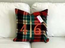 Load image into Gallery viewer, Felted Wool Blanket Pillow - Red, Green, Cream and Black plaid background. Incorporates fringe of original vintage blanket. Mottled rust colored numbers and cream CN Tower.