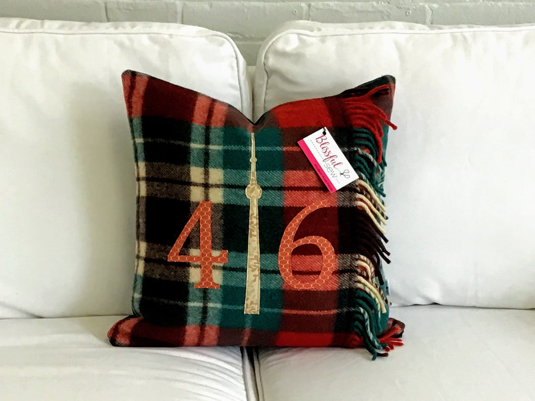 Felted Wool Blanket Pillow - Red, Green, Cream and Black plaid background. Incorporates fringe of original vintage blanket. Mottled rust colored numbers and cream CN Tower.