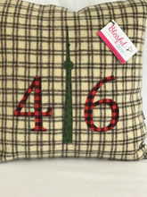 Load image into Gallery viewer, Cream pillow with chocolate brown squares. Red plaid numbers and green CN Tower.