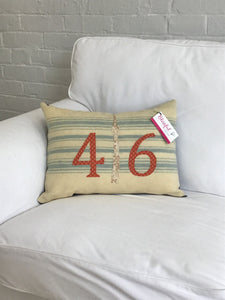 Cream pillow with blue stripes. Rust numbers and cream CN Tower