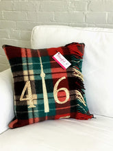"Load image into Gallery viewer, Felted Wool Blanket Pillow - Christmasy plaid background with mottled rust numbers and cream CN Tower. Incorporates the blanket fringe as soft adornment on front. Has the original blanket ""Highlander"" logo in the corner."