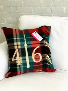 "Felted Wool Blanket Pillow - Christmasy plaid background with mottled rust numbers and cream CN Tower. Incorporates the blanket fringe as soft adornment on front. Has the original blanket ""Highlander"" logo in the corner."