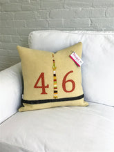 Load image into Gallery viewer, Cream pillow with modern black stripe. Rust numbers and coordinating CN Tower