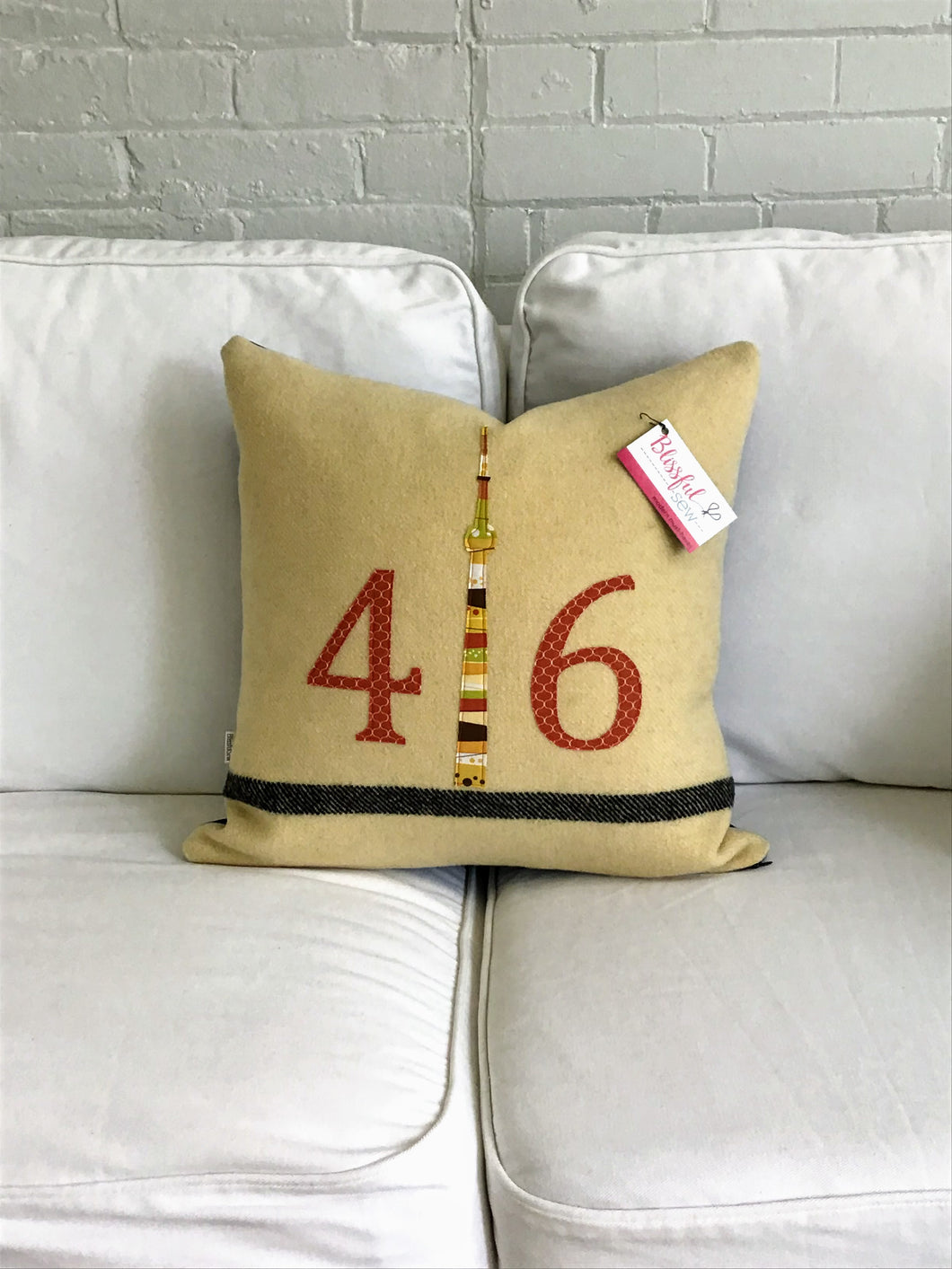 Cream pillow with modern black stripe. Rust numbers and coordinating CN Tower