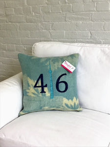 Modern aqua and cream pillow with navy numbers and teal CN Tower.