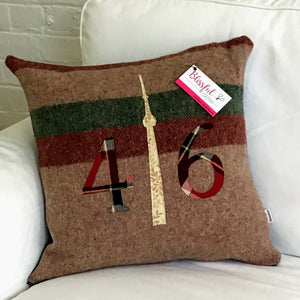 Light brown pillow with maroon and moss stripes. Maroon plaid numbers and cream CN Tower.