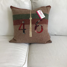 Load image into Gallery viewer, Light brown pillow with maroon and moss stripes. Maroon plaid numbers and cream CN Tower.